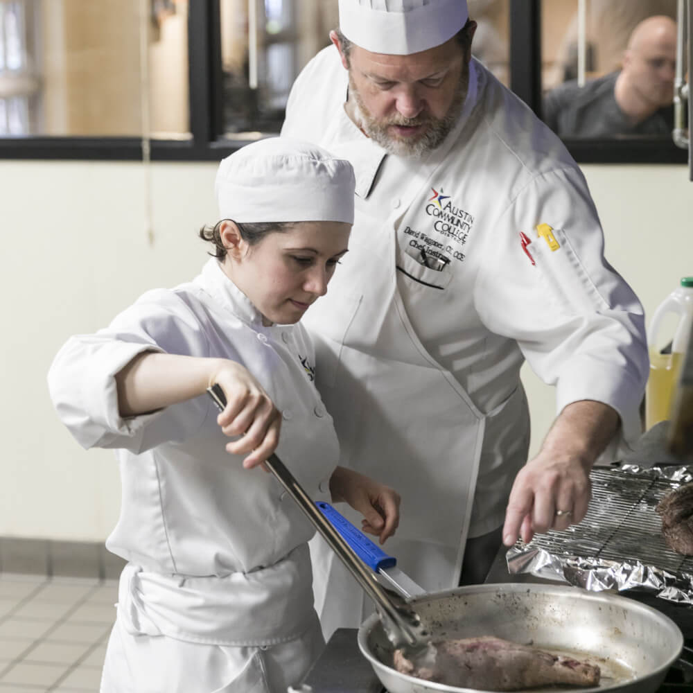 Culinary professor teaching a student