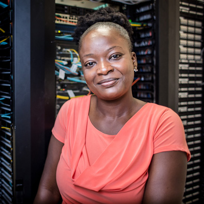 ACC IT alumna Aida Nacro poses for a portrait at her workplace.