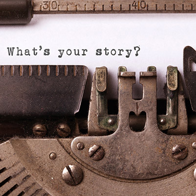The phrase what's your story? is typed on a sheet of paper in a typewriter