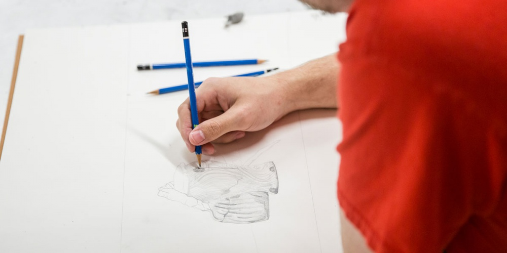 A person draws with a pencil.