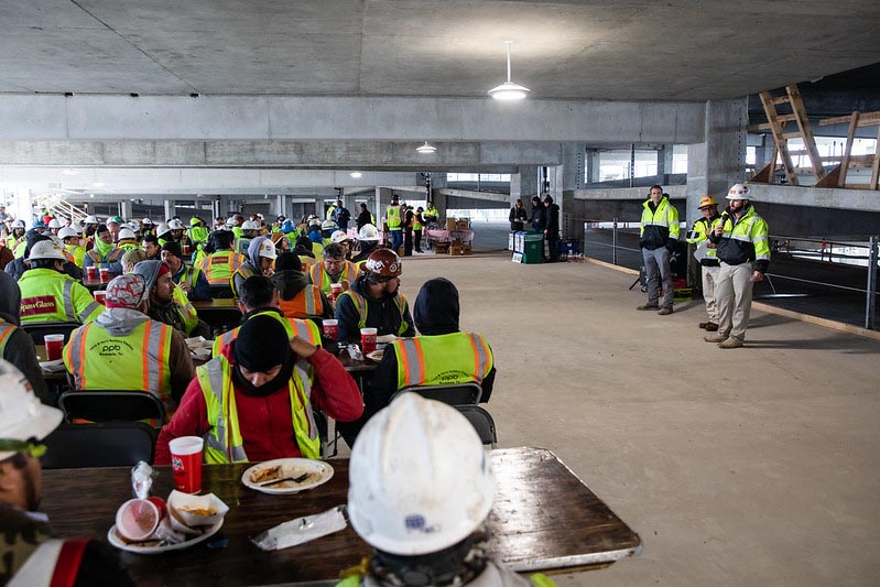 Members of the construction team that worked on the Highland campus Parking Garage attend a presentation during the topping out ceremony.