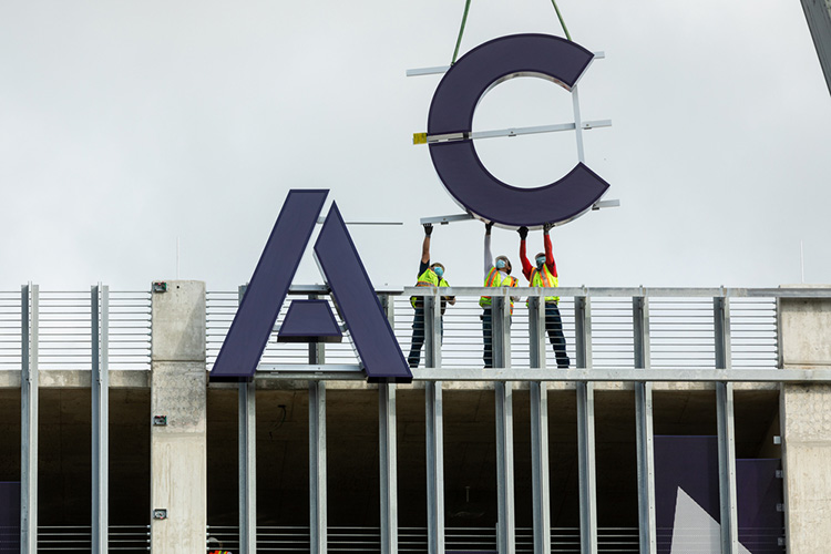 A large letter A and C being installed on the East facing side of the Highland Campus parking garage.