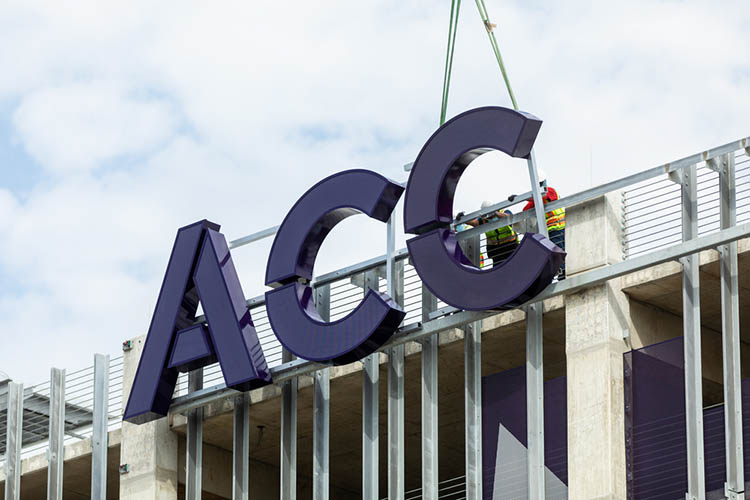 The letters ACC being installed on the East facing side of the Highland Campus parking garage.