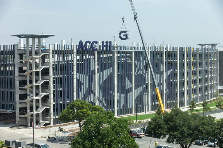 A crane lowers a large letter G next to the letters that will spell, ACC HIGHLAND, onto the East facing side of the Highland Campus parking garage.
