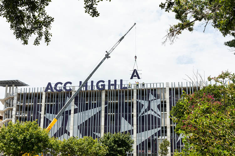 A crane lowers a large letter A next to the letters that will spell, ACC HIGHLAND, onto the East facing side of the Highland Campus parking garage.