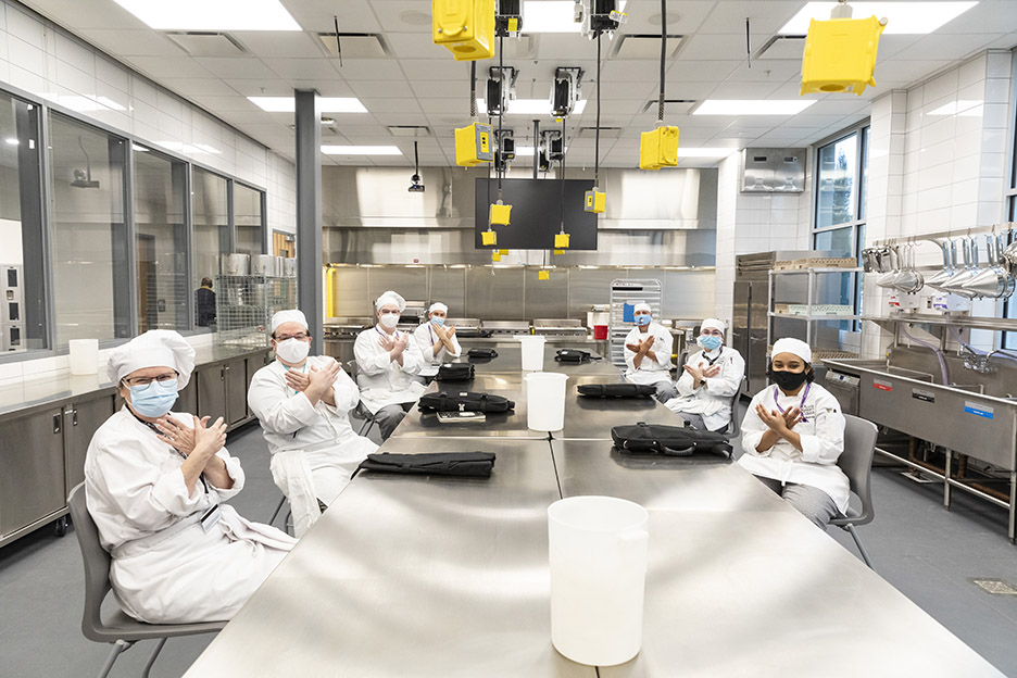 ACC Culinary Arts students pose for a photo in one of the commercial kitchens inside Highland Campus, Building 2000 where their first class of the spring 2021 semester, Meat Prep with Chef David Waggoner, is about to start.