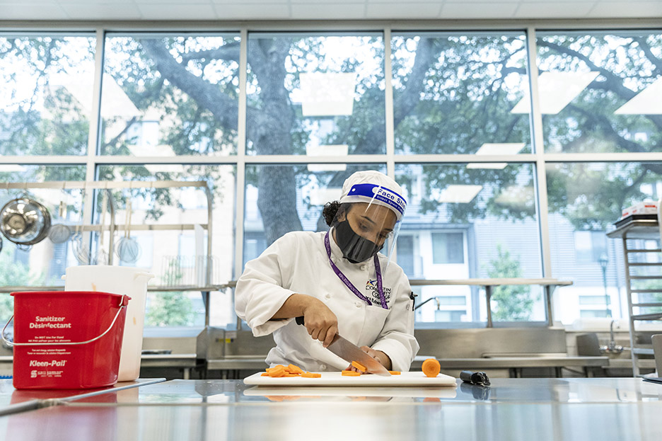 ACC Culinary Arts student Ora E. practices knife skills during her first class of the spring 2021 semester inside Highland Campus, Building 2000.