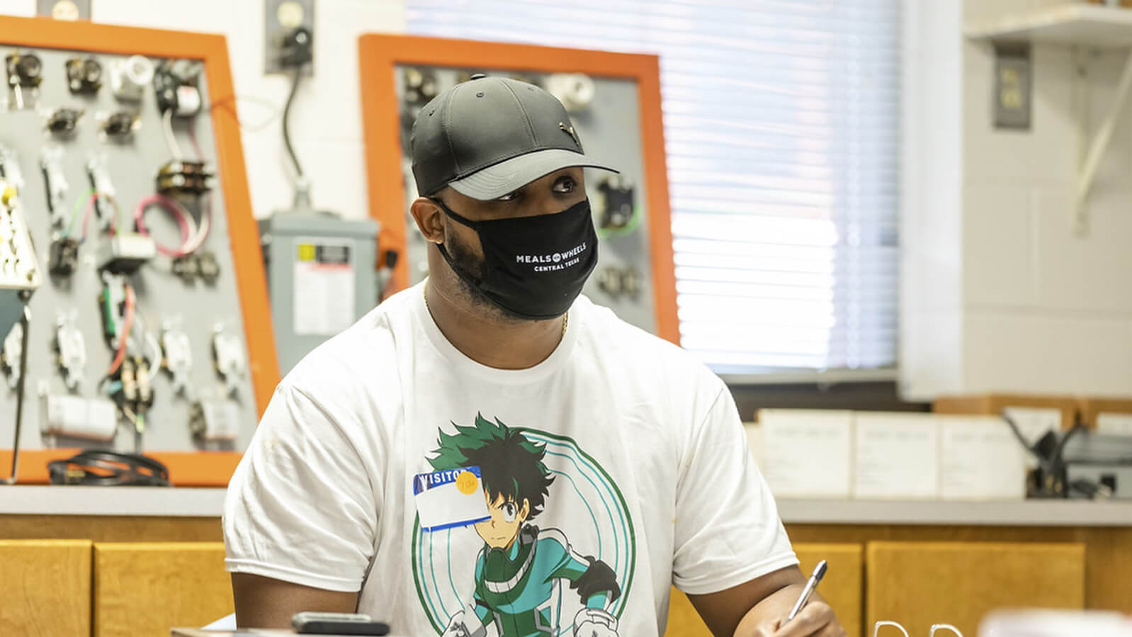 Kevin Jenkins takes notes during a class while wearing a mask.
