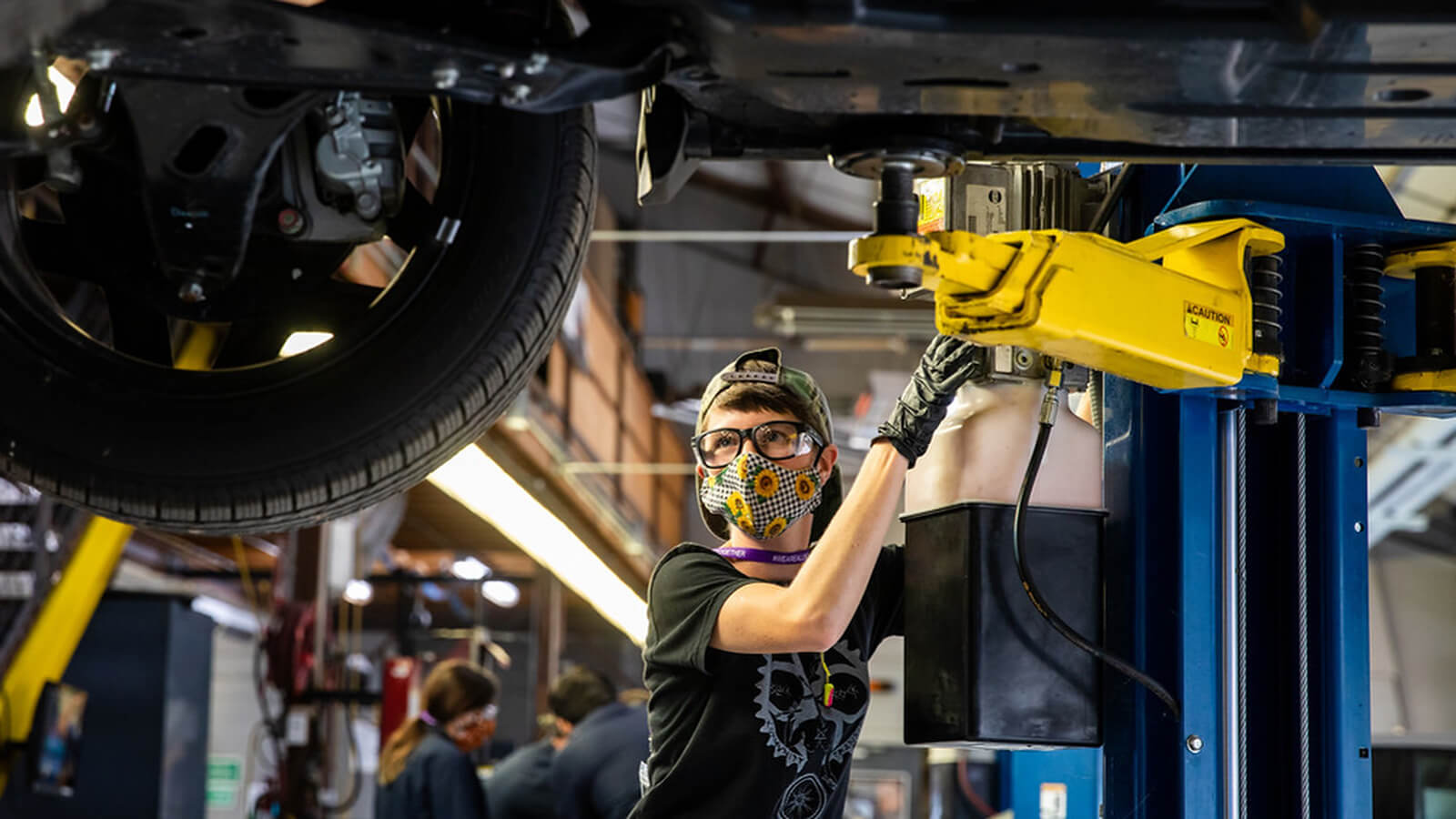 A student, wearing a mask, uses a car lift during an Automotive Technology class at the Riverside Campus.
