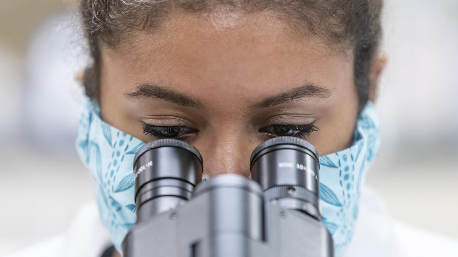 Brianna Fisher-Jones looks through a microscope while wearing a mask.