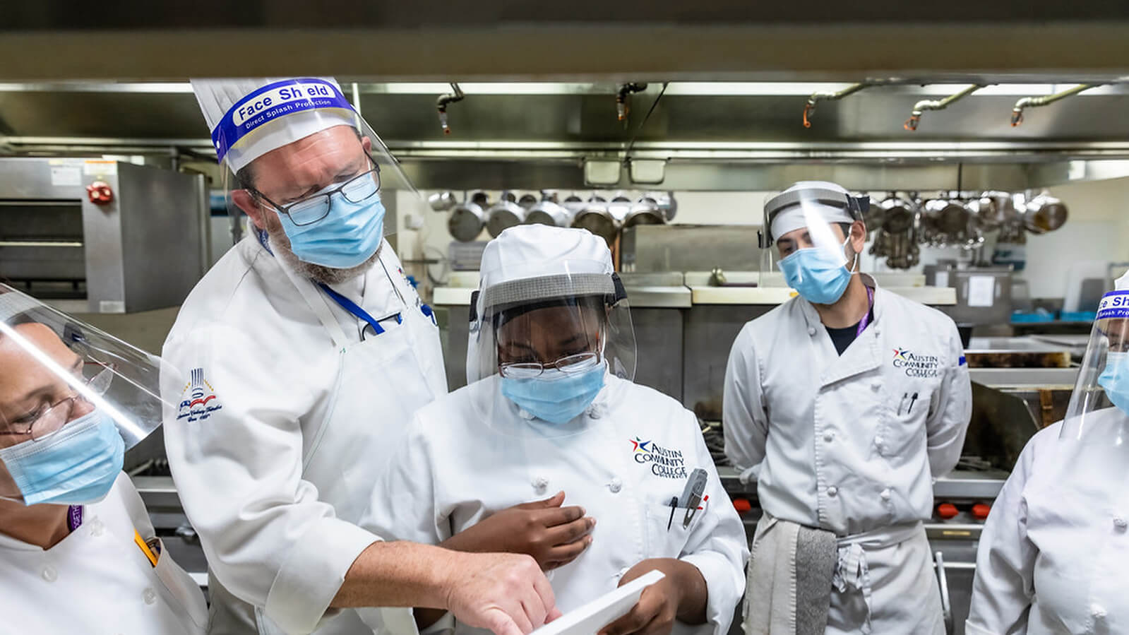 David Waggoner instructs students, Cathy Clayton, Alicia Jones, Robert Wilson, and Grace Aguilar, during a culinary class.