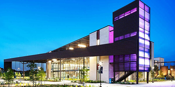 Building exterior at sunset with purple lighting.
