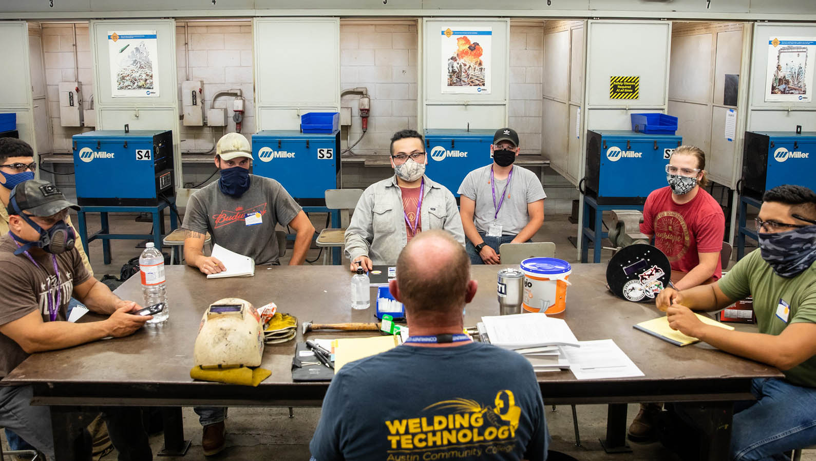 Students wearing masks listen to a lecture during a welding class.