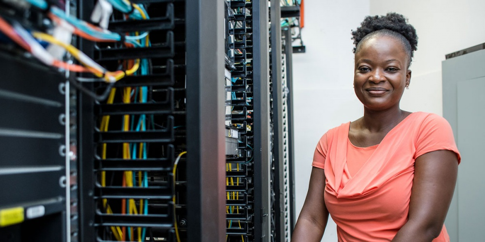 Lady working in a network server room.