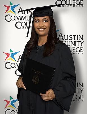 Female ACC graduate posing for portrait infront of a backdrop.