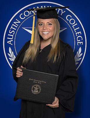 Female ACC graduate posing for portrait infront of a backdrop