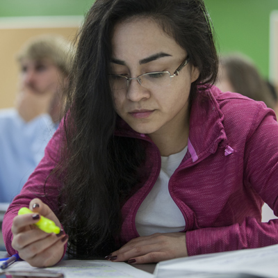 A female ACC student reads a book holding a highlighter.