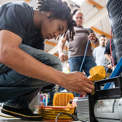 ACC student Byron Johnson works with HVAC equipment.